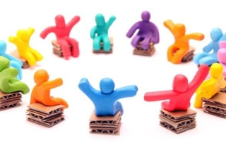 colorful clay people on cardboard seats sit in a circle