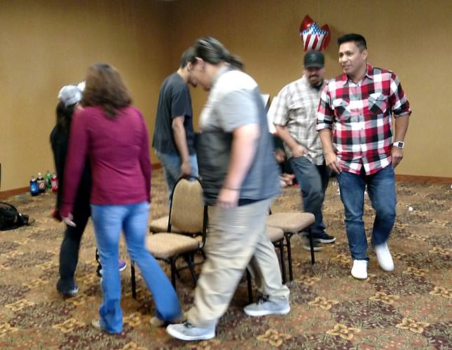 People circle around in game of musical chairs