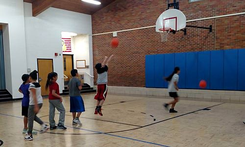 Kids line up to take turns shooting baskets in a gym