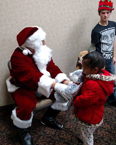 Santa Claus gives a teddy bear to a little girl