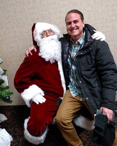 Smiling adult sits on Santa's knee