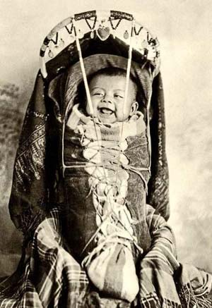 Laughing Native infant in a cradle board.