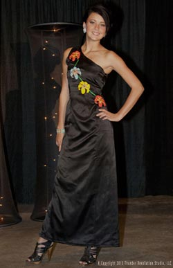 Woman models black gown with floral appliqués