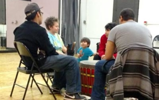 Youth seated around a drum with volunteer instructor