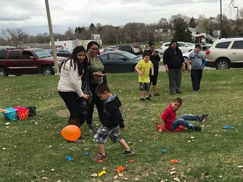 Kids chasing balloons in the balloon popping contest, cheered on by family members
