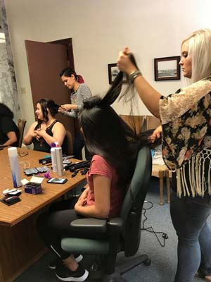 Volunteers doing hair for prom attendees at the Prep for Prom event