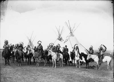 A group of Native Americans on horseback in front of several tipis.