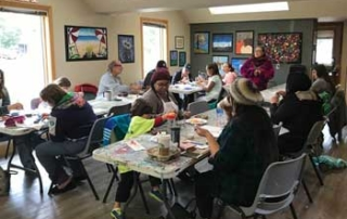 Community members at art studio painting rocks