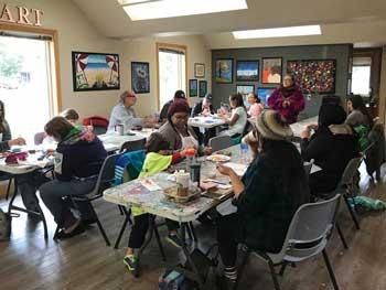 Community members at art studio painting rocks