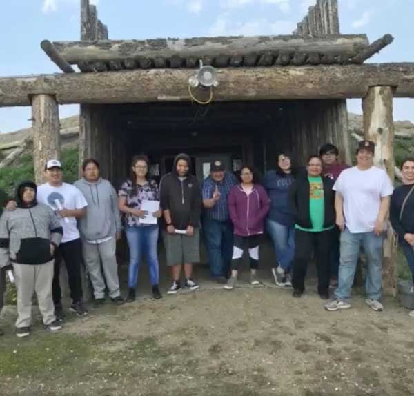 Youth pose in front of traditional earth lodge at Grandmother Earth Traditional Knowledge Camp