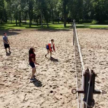 Kids playing volleyball in the park.