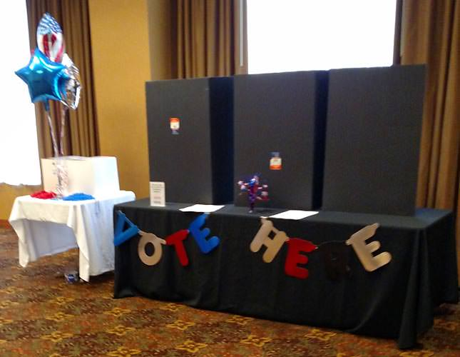 Mock voting booth decorated with banners and balloons