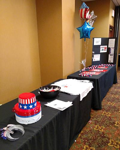 a table full of hats, visors, t-shirts, pens, candy, and other voting freebies