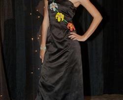 Woman models black gown with floral appliqués