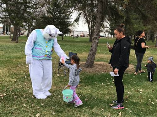 A little girl low-fives the Easter Bunny as her mother looks on