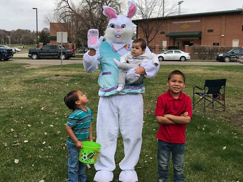 Easter Bunny holding a baby and waving at the SPRC Easter Egg Hunt