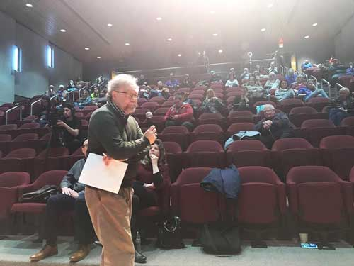 Dr. Brian Palacek speaks in front of an auditorium of people.