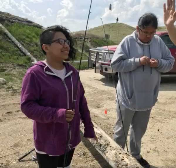 Youth holding fishing gear at Grandmother Earth Traditional Knowledge Camp
