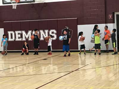 Kids in a gym practice basketball drills.