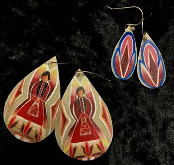 Two sets of drop-shaped earring painted in bright patterns rest on a black background.