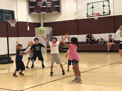 Young kids practicing their skills on the basketball court.
