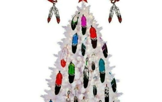 "A white Christmas Tree decorated with colorful Native feathers, a red star on top, and the words ""Merry Christmas."""