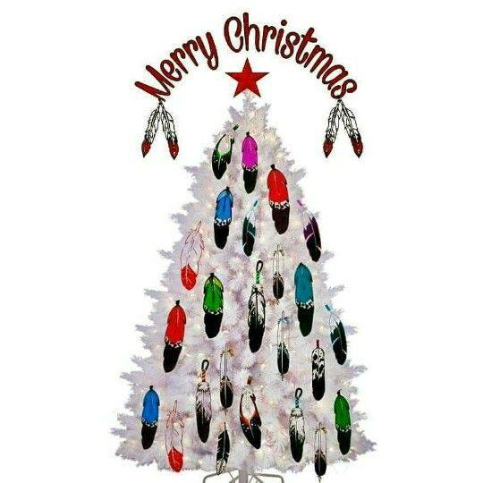 """A white Christmas Tree decorated with colorful Native feathers, a red star on top, and the words """"Merry Christmas."""""""